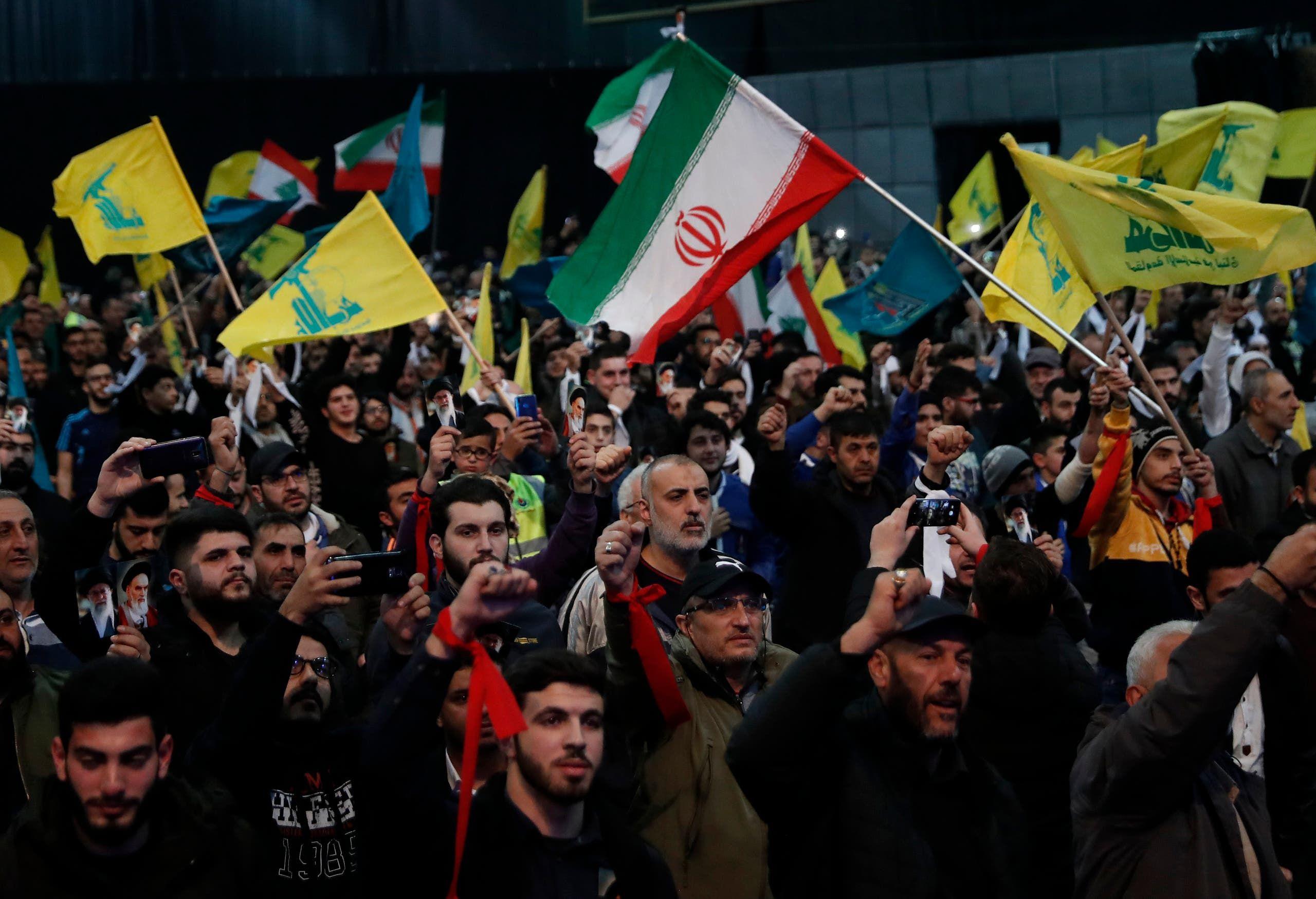 مناصرون لحزب الله يرفعون علمه والعلم الإيراني خلال تجمع في بيروت في 2019 (أرشيفية)