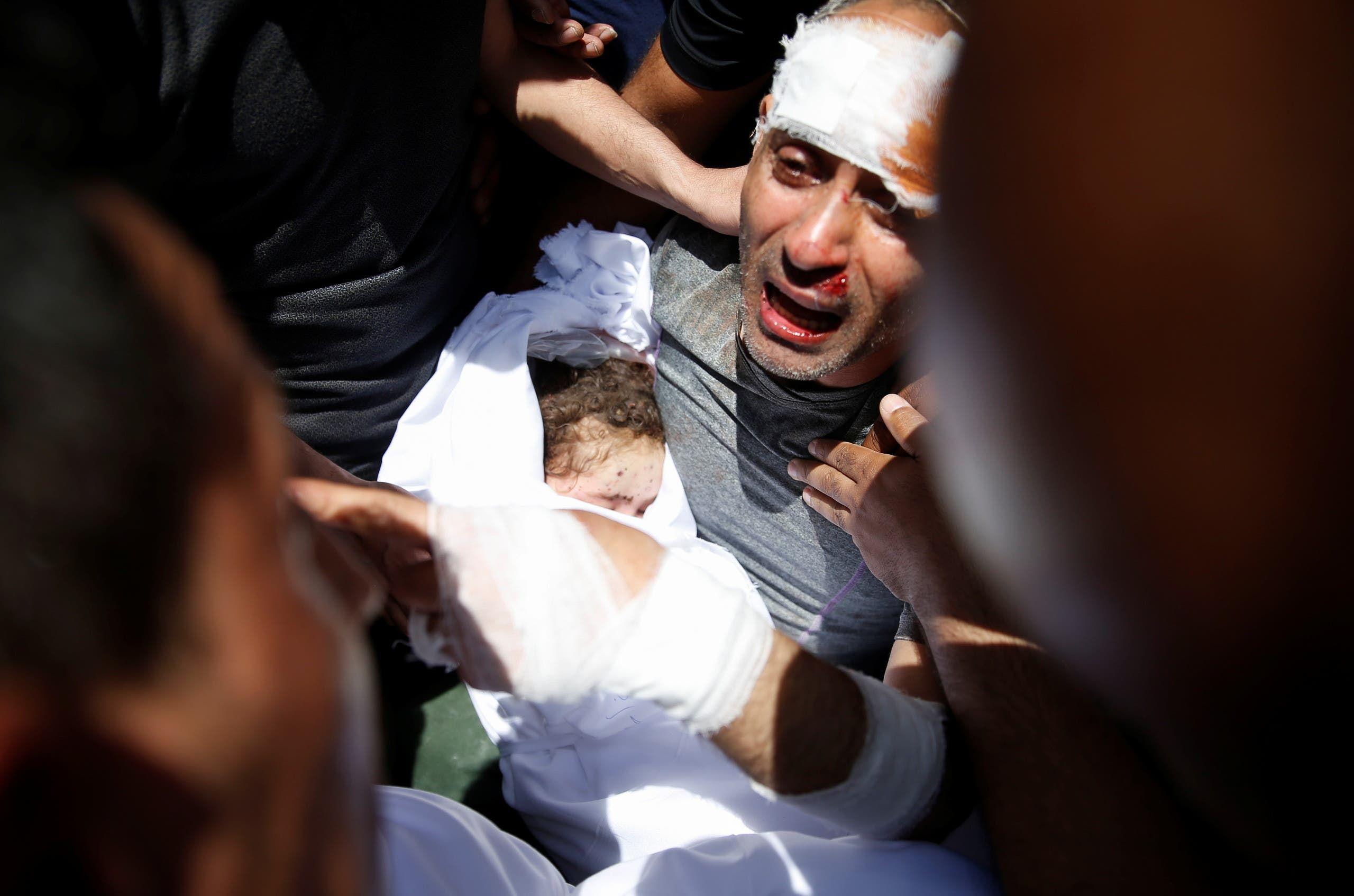 رجل يحمل جثة طفله المتوفي إثر غارة إسرائيلية في غزة
