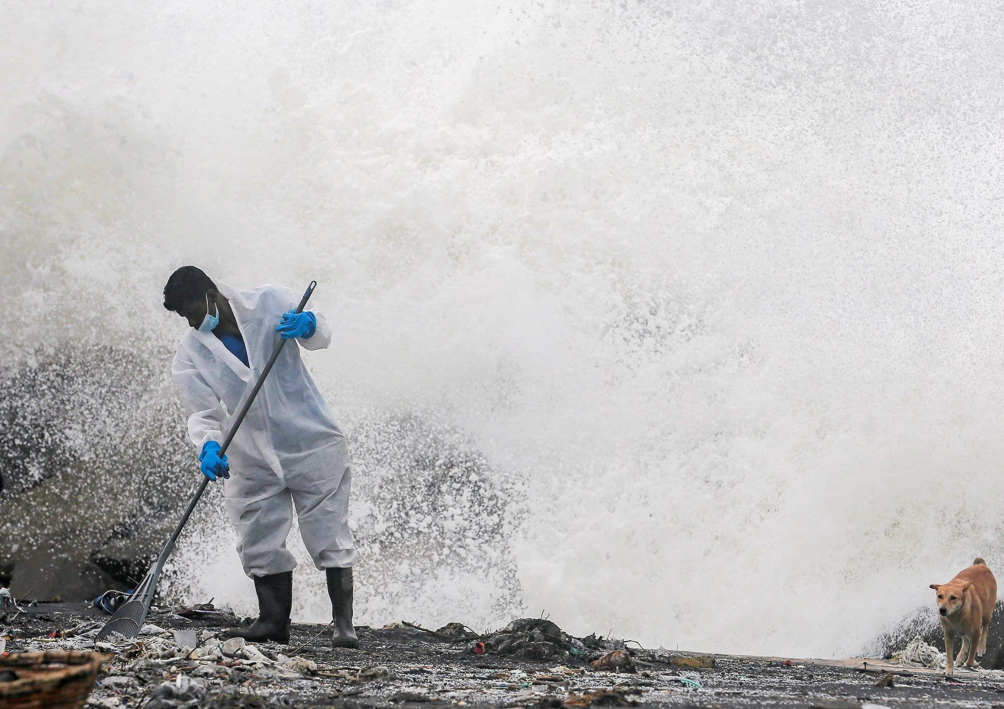 أحد أفراد البحرية السريلانكية يقوم بإزالة الحطام الذي وصل إلى الشاطئ من سفينة أكس - برس بيرل (أرشيفية من رويترز)