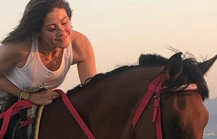 هيدي كرم على شاطئ البحر من فوق حصان